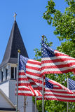 US flags waving outside white church steeple on Memorial Day. One nation under God Royalty Free Stock Images