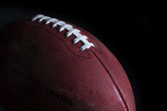 US Football. A regulation NFL leather US football in dramatic lighting and black background royalty free stock photos