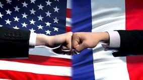 US gegen Frankreich-Konflikt, Krise der internationalen Beziehungen, Fäuste auf Flaggenhintergrund lizenzfreie stockfotos