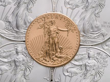 US Gold Eagle ontop of US Silver Eagles.  royalty free stock photos