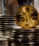 US Gold Eagle rests among piles of silver coins Stock Photography