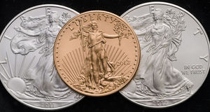 US Gold Eagle on 2 US Silver Eagles w/ Black background.  stock image