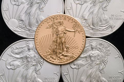 US Gold Eagle on 4 US Silver Eagles w/ Black background.  stock photo