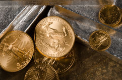 US Gold Eagles on Silver Bars. American Gold Eagle Coins with laying on Silver bars royalty free stock photography