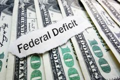 US government federal deficit. Federal Deficit newspaper scrap on hundred dollar bills Stock Photo