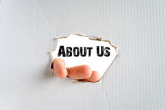 About Us. Hand and place for text on the cardboard background royalty free stock image