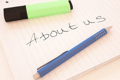 About us. Handwritten text in a notebook on a desk - 3d render illustration Stock Images