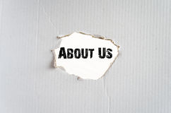 About Us. A hole in the paper and place for conceptual text stock photos