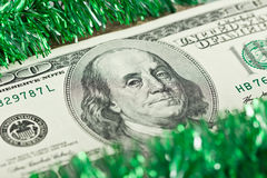 US hundred dollar bill with a Christmas tinsel Stock Photos