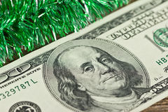 US hundred dollar bill with green Christmas tinsel Royalty Free Stock Images