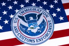 US Immigration and Customs Enforcement. LONDON, UK - MARCH 26TH 2018: The symbol of US Immigration and Customs Enforcement portrayed with the US flag, on 26th stock photography