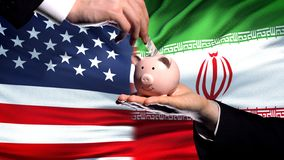 US investment in Iran, hand putting money in piggybank on flag background. Stock photo royalty free stock photos