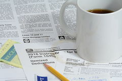 US IRS tax forms with coffee. US IRS 1040 tax forms with pencil and receipts and instructions for itemized deductions with spilled coffee stain ring Royalty Free Stock Photography