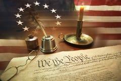 US-Konstitution mit Federkiel, Gläsern, Kerze, Tinte und Flagge Stockbild