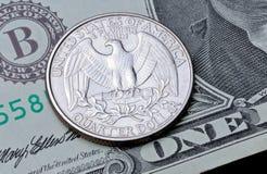US-Münzenvierteldollar auf einem Dollarschein Stockbilder