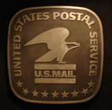 US Mail. United States Postal Service sign with stars and eagle on a black background illuminated from the top right - USA Royalty Free Stock Image