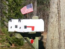 US mail boxes with flag. Two white US mail boxes with US flag stock photo