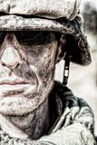 US Marine badass. Location shot of United States Marine with rifle weapons in uniforms. Military equipment, army helmet, warpaint, smoked dirty face, tactical Royalty Free Stock Image