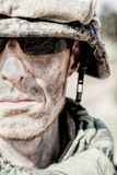 US Marine badass. Location shot of United States Marine with rifle weapons in uniforms. Military equipment, army helmet, warpaint, smoked dirty face, tactical Stock Images
