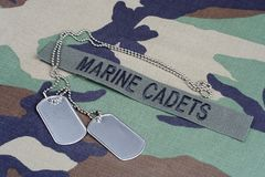 US MARINE CADETS branch tape and dog tags on woodland camouflage uniform. Background Stock Photos