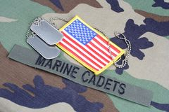 US MARINE CADETS branch tape, flag patch and dog tags on woodland camouflage uniform. Background Royalty Free Stock Images