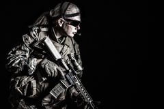 US Marine Soldier. Studio shot of United States Marine with rifle weapons in uniforms. Military equipment, army helmet, combat boots, tactical gloves. Isolated Stock Photos