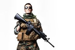 US Marine Soldier. Studio shot of United States Marine with rifle weapons in uniforms. Military equipment, army helmet, combat boots, tactical gloves. Isolated Royalty Free Stock Images