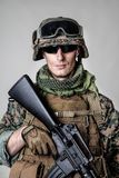 US Marine Soldier. Studio shot of United States Marine with rifle weapons in uniforms. Military equipment, army helmet, combat boots, tactical gloves. Isolated Royalty Free Stock Photography