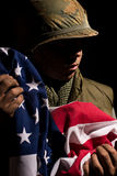US Marine Vietnam War holding American flag. US Marine from the Vietnam War period holding the American Stars and Stripes flag. The young soldier is covered in stock photo
