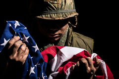 US Marine Vietnam War holding American flag. US Marine from the Vietnam War period holding the American Stars and Stripes flag. The young soldier is covered in Royalty Free Stock Photos