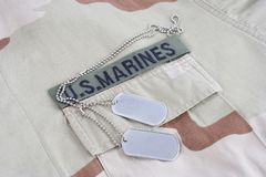 US MARINES branch tape with dog tags on desert camouflage uniform. Background Royalty Free Stock Photos