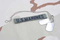 US MARINES branch tape with dog tags on desert camouflage uniform. Background Stock Photos