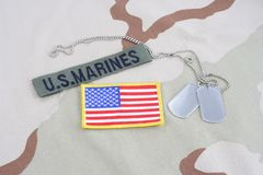 US MARINES  branch tape with dog tags and flag patch on desert camouflage uniform. US MARINES branch tape with dog tags and flag patch on desert camouflage Royalty Free Stock Photography