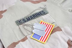 US MARINES  branch tape with dog tags and flag patch on desert camouflage uniform. Background Stock Image