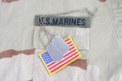 US MARINES  branch tape with dog tags and flag patch on desert camouflage uniform. Background Stock Photo