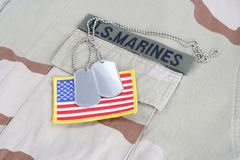 US MARINES branch tape with dog tags and flag patch on desert camouflage uniform royalty free stock image