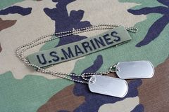US MARINES branch tape and dog tags on woodland camouflage uniform. Background Royalty Free Stock Photography