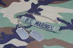 US MARINES branch tape and dog tags on woodland camouflage uniform. Background Stock Image