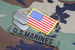 US MARINES branch tape, flag patch and dog tags on woodland camouflage uniform. Background Royalty Free Stock Photo