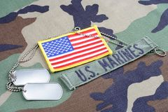 US MARINES branch tape, flag patch and dog tags on woodland camouflage uniform. Background Royalty Free Stock Images