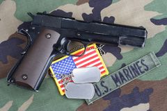 US MARINES branch tape, M1911 handgun with dog tags on woodland camouflage uniform. Background Royalty Free Stock Images