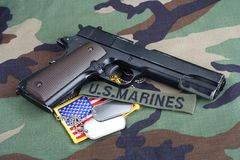 US MARINES branch tape, M1911 handgun with dog tags on woodland camouflage uniform. Background Royalty Free Stock Image