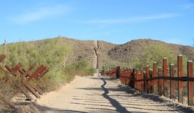 US - Mexican Border in Sonoran Desert. This border bollard barrier is located west of Lukeville, Arizona and Sonoyta, Mexico. The road is used by US Border Royalty Free Stock Photos