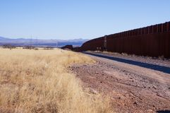 The US-Mexico border wall in Arizona desert. The US-Mexico border wall and gravel road in sunny Arizona desert stock photos