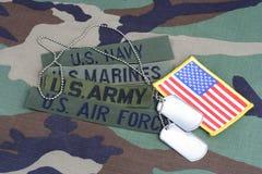 US-Militärkonzept mit Niederlassungsbändern und Erkennungsmarken auf Waldland tarnen Uniform Lizenzfreies Stockfoto