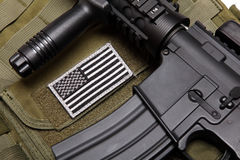 US military concept. Tactical vest with U.S. battle flag and assault rifle with tactical grip close-up. Studio shot Stock Photography