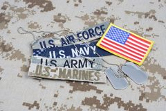 US MILITARY concept with branch tapes and dog tags on camouflage uniform royalty free stock photography