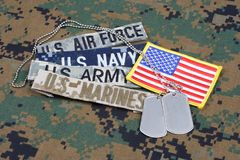 US MILITARY concept with branch tapes and dog tags on camouflage uniform royalty free stock photo