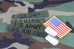 US military concept with branch tapes and dog tags on woodland camouflage uniform. Background royalty free stock photo