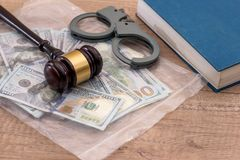 Us Money with wooden hammer handcuffs. Law  book Stock Image